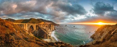 여름, 몬트레이 카운티, 캘리포니아, 미국에서 극적인 cloudscape와 일몰 아름 다운 황금 저녁 빛에 세계 유명한 고속도로 1 함께 역사적인 Bixby 크릭 브릿지의 아름 다운 파노라마보기 스톡 콘텐츠 - 98272249