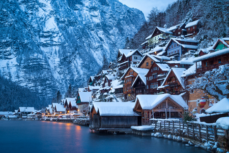 Classic postcard view of traditional wooden houses in famous Hallstatt lakeside town in the Alps in mystic twilight during blue hour at dawn on a beautiful cold foggy day in winter, Salzkammergut region, Austria Stock Photo