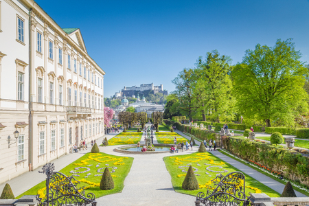 Tourists walking through famous Mirabell Gardens with famous Hohensalzburg Fortress in the background on a sunny day with blue sky and clouds in summer, Salzburg, Salzburger Land, Austria