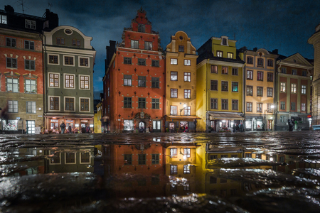 Classic view of colorful houses at famous Stortorget town square in Stockholms historic Gamla Stan (Old Town) reflecting in a puddle with blue sky, central Stockholm, Sweden