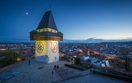 Panoramic aerial view of the old town of Graz with famous Grazer Uhrturm (clock tower) illuminated in beautiful evening twilight during blue hour at dusk, Styria, Austria