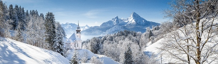 Panoramic view of beautiful winter landscape in the Bavarian Alps with pilgrimage church of Maria Gern and famous Watzmann massif in the background, Nationalpark Berchtesgadener Land, Bavaria, Germany 版權商用圖片 - 98416459