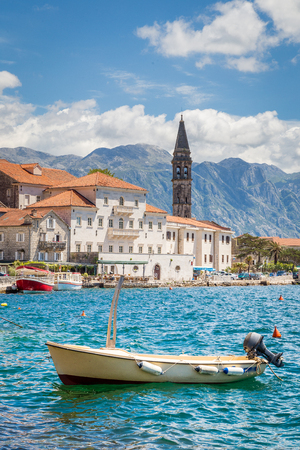 Scenic panorama view of the historic town of Perast at world famous Bay of Kotor on a beautiful sunny day with blue sky and clouds in summer, Montenegro, southern Europe
