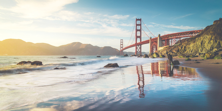 Classic panoramic view of famous Golden Gate Bridge seen from scenic Baker Beach in beautiful golden evening light on a sunny day with blue sky and clouds in summer, San Francisco, California, USA Stock Photo - 98416222