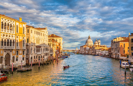 Classic panoramic view of famous Canal Grande with scenic Basilica di Santa Maria della Salute in beautiful golden evening light at sunset, Venice, Italy Stock Photo