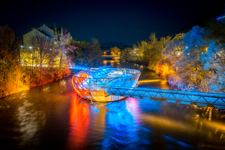 Beautiful panorama view of famous Grazer Murinsel, an artificial floating island in the middle of Mur river illuminated at night, Graz, Styria region, Austria Editorial