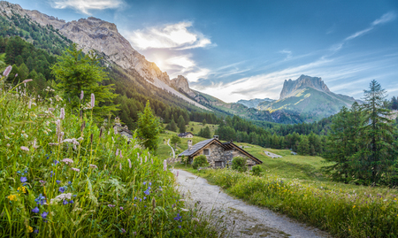 Beautiful view of idyllic alpine mountain scenery with traditional old mountain chalets and fresh green meadows on a sunny day with blue sky and clouds in springtime, South Tyrol, Italy Stock Photo