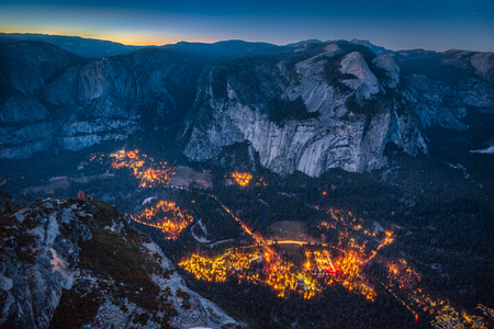Panoramic aerial birds eye view of famous Yosemite Valley illuminated in beautiful post sunset twilight during blue hour at dusk in summer, Yosemite National Park, Mariposa County, California, USA Stock Photo