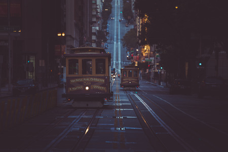 Classic view of historic traditional Cable Cars riding on famous California Street in beautiful early morning twilight at dawn in summer with retro vintage style cross processing filter effect, San Fr 스톡 콘텐츠