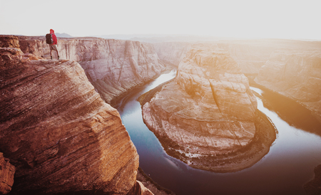 Panoramic view of a fearless male hiker standing on a steep cliff while overlooking famous Horseshoe Bend in beautiful golden evening light at sunset, Page, Arizona, USA Stock Photo
