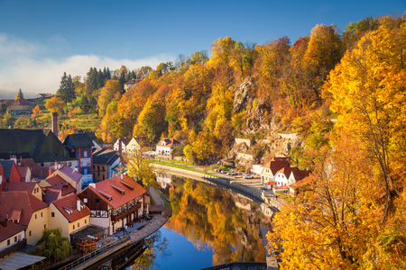 Panoramic view of the historic city of Cesky Krumlov, in beautiful golden morning light at sunrise with mystic fog in fall, Czech Republic Фото со стока