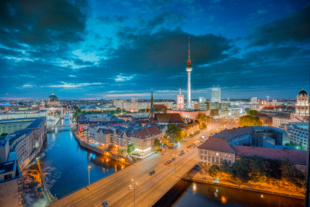 Aerial panorama twilight view of Berlin skyline with famous TV tower and Spree river illuminated during blue hour at dusk with dramatic clouds, Germany 写真素材