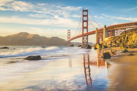 Vista panorámica clásica del famoso puente Golden Gate visto desde la pintoresca playa de Baker en la hermosa luz dorada del atardecer en un día soleado con cielo azul y nubes en verano, San Francisco, California, EE. UU.