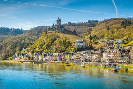 Beautiful view of the historic town of Cochem with famous Reichsburg castle on top of a hill and scenic Moselle river on a sunny day with blue sky and clouds in springtime, Rheinland-Pfalz, Germany