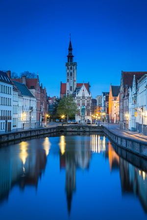 Beautiful panoramic view of famous Spiegelrei canal with famous Poortersloge and Jan van Eyck square in the background illuminated during blue hour at dusk, Brugge, Flanders region, Belgium 版權商用圖片