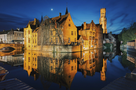 Classic postcard view of the historic city center of Brugge, often referred to as The Venice of the North, with famous Rozenhoedkaai illuminated in beautiful twilight, West Flanders province, Belgium Фото со стока