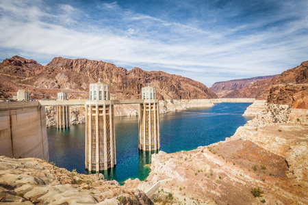 Classic view of famous Hoover Dam, a major tourist attraction located on the border between the states of Nevada and Arizona, on a beautiful sunny day with blue sky and clouds in summer, USA