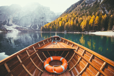 Beautiful view of traditional wooden rowing boat on scenic Lago di Braies in the Dolomites in scenic morning light at sunrise, South Tyrol, Italy Banco de Imagens