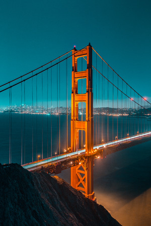 Classic vertical view of famous Golden Gate Bridge seen from Battery Spencer viewpoint in beautiful post sunset twilight during blue hour at dusk in summer, San Francisco, California, USA