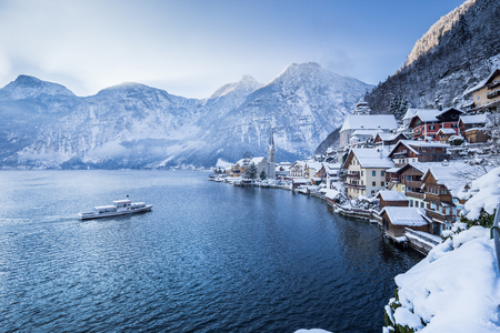 Classic postcard view of famous Hallstatt lakeside town with traditional passenger ship on Hallstattersee lake on a beautiful morning with blue sky and fog in winter, Salzkammergut, Austria