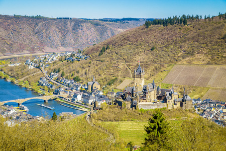 Beautiful aerial view of the historic town of Cochem with famous Reichsburg castle on top of a hill and scenic Moselle river on a sunny day with blue sky in spring, Rheinland-Pfalz, Germany