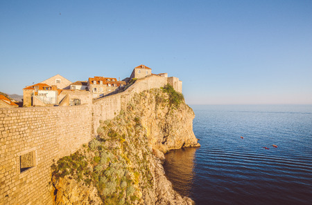 Panoramic view of the old town of Dubrovnik with calm sea in beautiful golden evening light at sunset with blue sky in summer, Dalmatia, Croatia Stock Photo
