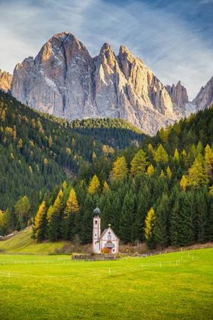 Schöne Ansicht der historischen Kirche von St. Johann von Nepomuk mit berühmten Odle Group Berggipfeln in den Dolomiten im schönen Abendlicht bei Sonnenuntergang, Südtirol, Italien Standard-Bild