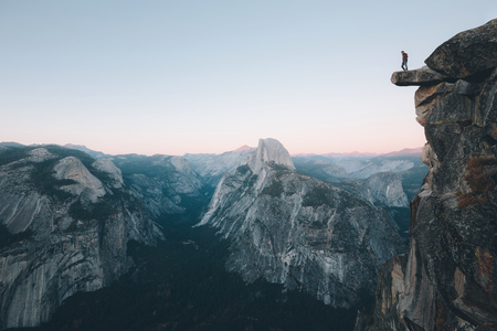 A fearless hiker is standing on an overhanging rock enjoying the view towards famous Half Dome at Glacier Point overlook in beautiful post sunset twilight, Yosemite National Park, California, USA Stock Photo