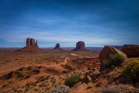 Classic panoramic view of scenic Monument Valley with the famous Mittens and Merrick Butte illuminated in beautiful mystic moonlight on a starry night in summer, Arizona, American Southwest, USA 写真素材