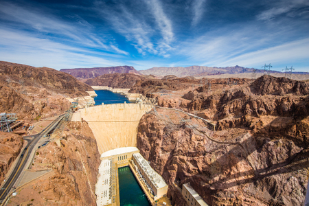 Aerial wide angle view of famous Hoover Dam, a major tourist attraction located on the border between the states of Nevada and Arizona, on a beautiful sunny day with blue sky and clouds in summer, USA Stock fotó