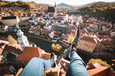 Aerial birds eye view of young rooftop climber sitting on the edge of a high rise tower dangling his feet high above the historic town of Cesky Krumlov, Bohemia, Czech Republic Stock Photo - 100199070
