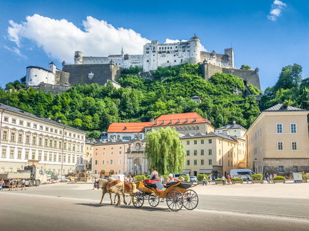 Beautiful panoramic view of the historic city of Salzburg with traditonal horse-drawn Fiaker carriage and famous Hohensalzburg Fortress on a hill on a sunny day with blue sky and clouds in summer