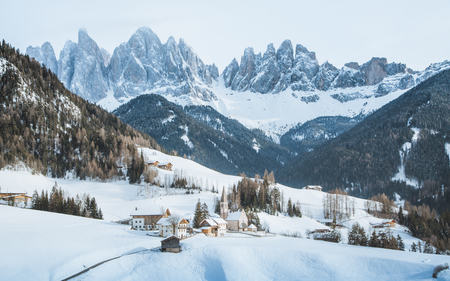 Classic panoramic view of famous Dolomites mountain peaks with the historic village of Val di Funes on a scenic day in winter, South Tyrol, Italy Stock Photo