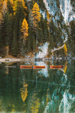 Beautiful panoramic view of traditional wooden rowing boats and historic chapel reflecting in scenic Lago di Braies in the Dolomites, South Tyrol, Italy