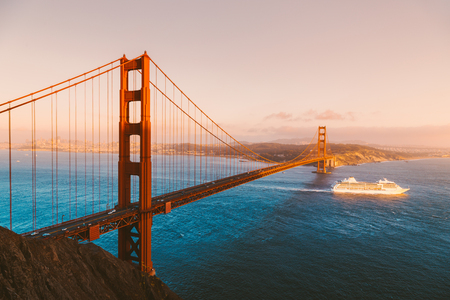 Beautiful panorama view of cruise ship passing famous Golden Gate Bridge with the skyline of San Francisco Stock Photo