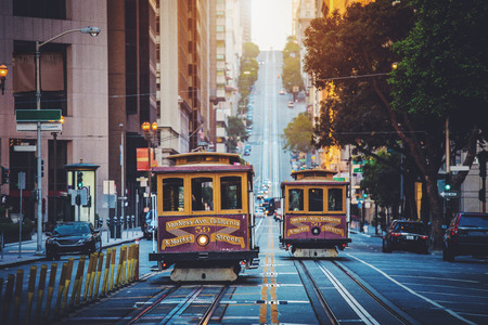 Classic view of historic traditional Cable Cars riding on famous California Street