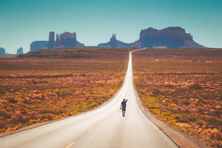 Classic panorama view of young man walking on famous Forrest Gump Road in Monument Valley at noon, Utah, American West, USA