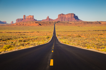 Classic panorama view of historic U.S. Route 163 running through famous Monument Valley