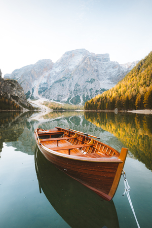 Beautiful view of traditional wooden rowing boat on scenic Lago di Braies in the Dolomites in scenic morning light at sunrise, South Tyrol, Italy Фото со стока