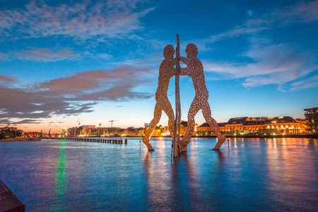 JULY 21, 2015 - BERLIN: Panoramic view of Berlin skyline with famous Molecule Man sculpture and Spree river in beautiful post sunset twilight at dusk in summer