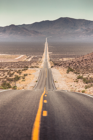 Classic panorama view of an endless straight road running through the barren scenery