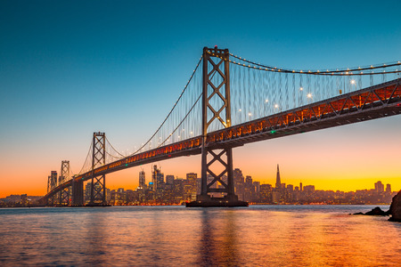 Classic panoramic view of San Francisco skyline with famous Oakland Bay Bridge illuminated in beautiful golden evening