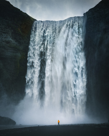 Panorama view of hiker in yellow rain jacket standing in front of gigantic Skogafoss waterfall on a moody day with dark clouds in summer, Skogar, Iceland