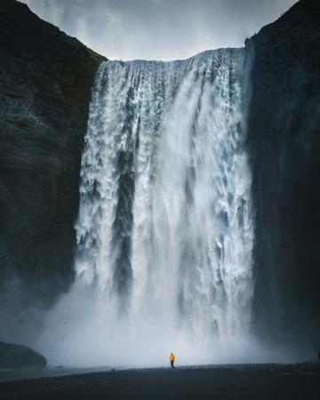 Vue panoramique du randonneur en veste de pluie jaune debout devant la gigantesque cascade de Skogafoss un jour maussade avec des nuages sombres en été, Skogar, Islande Banque d'images