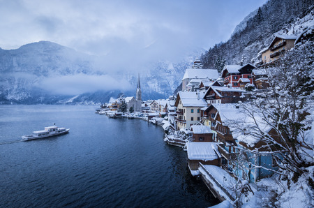 Classic postcard view of famous Hallstatt lakeside town with traditional passenger ship Banco de Imagens