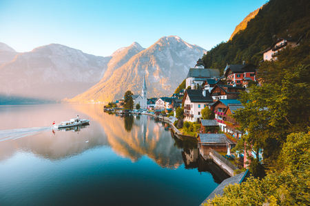 Classic postcard view of famous Hallstatt lakeside town in the Alps with traditional passenger ship Stock Photo