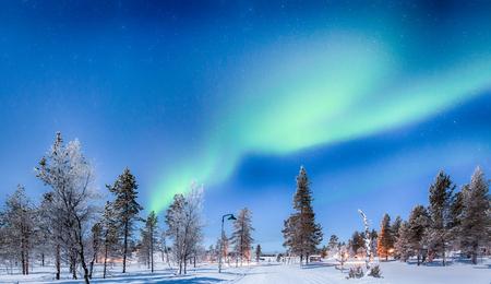 Panoramic view of amazing Aurora Borealis northern lights over beautiful winter wonderland