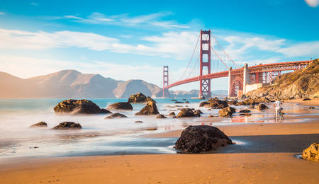 Classic panoramic view of famous Golden Gate Bridge seen from scenic Baker Beach in beautiful golden evening light