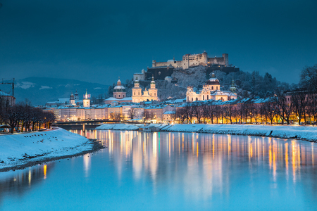 Classic view of the historic city of Salzburg with famous Festung Hohensalzburg and Salzach river illuminated in beautiful twilight