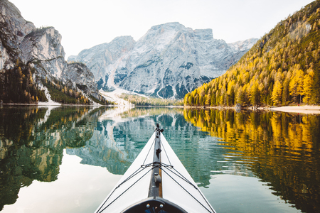 Beautiful view of kayak on a calm lake with amazing reflections of mountain peaks and trees with yellow autumn foliage in fall, Lago di Braies, Italy Banco de Imagens